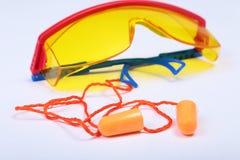 Оранжевые беруш и защитные стекла Беруш для уменьшения шума на белой предпосылке Стоковые Фото