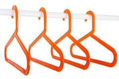 Оранжевые вешалки на штанге изолированной на белизне Стоковая Фотография RF