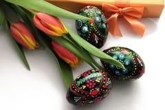 Оранжевые желтые тюльпаны, покрасили пасхальные яйца и подарочную коробку стоковое фото rf