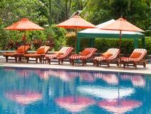 Оранжевые зонтики и кровать на бассейне Стоковые Фото