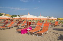 Оранжевые зонтики и салоны фаэтона на пляже Римини в ем стоковые изображения