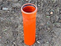 Оранжевые канализационные трубы стоя вертикально в земле стоковое фото