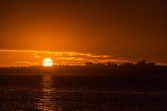 Оранжевые оттенки тропического захода солнца над водой с silhoue городского пейзажа Стоковое фото RF