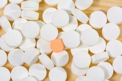 Оранжевые пилюльки на куче белых пилюлек Стоковая Фотография
