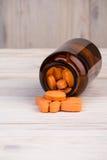 Оранжевые пилюльки в коричневой стеклянной таре Стоковое Фото