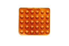 Оранжевые пилюльки в пакете волдыря изолированном на белизне Стоковое Изображение