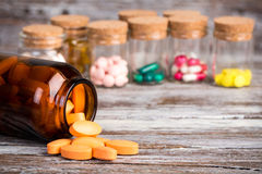 Оранжевые пилюльки в стеклянной таре с другими пилюльками в предпосылке Стоковая Фотография