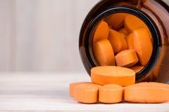 Оранжевые пилюльки в стеклянной таре Стоковая Фотография