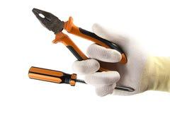 Оранжевые плоскогубцы отвертки и плоск-носа в руке в перчатке изолированной на белой предпосылке Стоковое фото RF