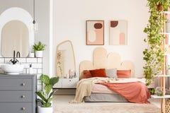 Оранжевые подушки на кровати рядом с зеркалом в современном interio спальни Стоковая Фотография RF