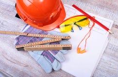 Оранжевые трудная шляпа, беруш, защитные стекла и перчатки для работы Беруш для уменьшения шума на белой предпосылке Стоковая Фотография