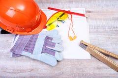 Оранжевые трудная шляпа, беруш, защитные стекла и перчатки для работы Беруш для уменьшения шума на белой предпосылке Стоковые Изображения RF
