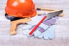 Оранжевые трудная шляпа, беруш, защитные стекла и перчатки для работы Беруш для уменьшения шума на белой предпосылке Стоковое фото RF