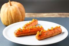 оранжевые eclairs на белых плите и тыкве Стоковая Фотография RF