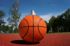 Оранжевый баскетбол против голубого облачного неба Стоковое Фото