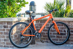 Оранжевый велосипед кирпичной стеной Стоковое Изображение