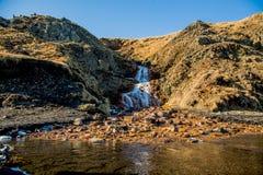 Оранжевый водопад снизу, обрамленный утесом стоковая фотография