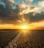 Оранжевый заход солнца в низких драматических облаках над дорогой асфальта стоковые фотографии rf