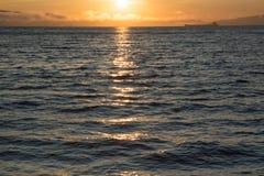 Оранжевый заход солнца и темная вода Стоковая Фотография RF