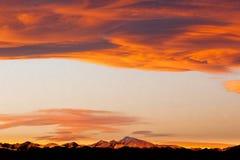 Оранжевый заход солнца над скалистыми горами стоковые изображения