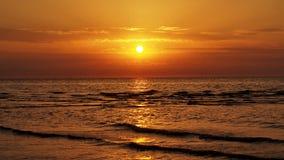 Оранжевый заход солнца и облака на море Стоковое Изображение RF