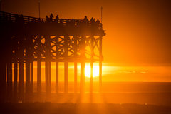 Оранжевый заход солнца на пляже с пристанью Тень пристани и людей на пристани Стоковые Изображения