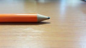 Оранжевый карандаш на деревянном столе Стоковые Фотографии RF