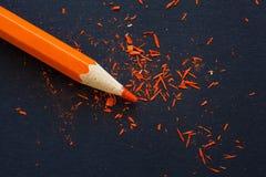Оранжевый карандаш на черноте стоковое изображение rf