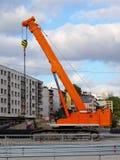Оранжевый кран на гусеничном ходе на месте работ строительства дорог в городе на фоне жилого дома и s стоковые фото