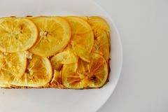 Оранжевый пирог на белой плите с апельсинами Стоковая Фотография RF