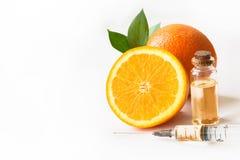 Оранжевый плодоовощ куска, пластичный устранимый шприц и бутылка с маслом или сутью Изолировано на белизне конец вверх Стоковая Фотография RF