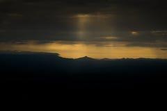 Оранжевый свет тот блески через облака В вечере Стоковое Изображение