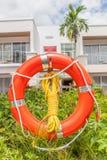 Оранжевый томбуй жизни с узлом веревочки висит рядом гостиницу Стоковые Фотографии RF