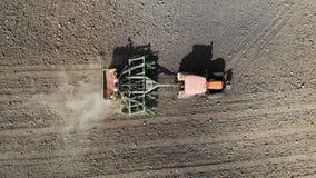 Оранжевый трактор вспахивает поле вид с воздуха сток-видео