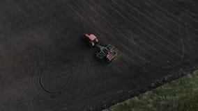 Оранжевый трактор вспахивает поле вид с воздуха видеоматериал
