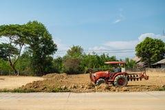 Оранжевый трактор работает стоковые фотографии rf