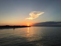 Оранжевый шарик солнца завишет любяще над спокойными водами пляжа Pensacola стоковое изображение rf
