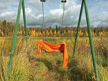 Оранжевый шарф забытый на качании стоковые изображения