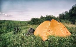 Оранжевый шатер с рюкзаком и велосипедом на зеленом луге Стоковые Изображения RF