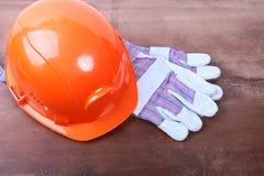 Оранжевый шлем инженера безопасности на коричневой предпосылке Стоковые Фото