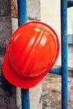 Оранжевый шлем повешенный на голубых лесах Стоковые Изображения