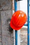 Оранжевый шлем повешенный на голубых лесах Стоковое Изображение