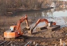 2 оранжевых землекопа работают на дне пруда стоковые фотографии rf