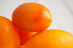 4 оранжевых томата на белом деревянном столе Стоковое Изображение