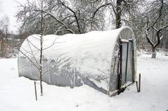 Оранжерея парника Snowy пластичная в саде середины зимы Стоковое Изображение RF