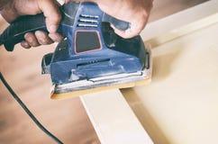 Орбитальный шлифовальный прибор в пользе, зашкурить старая дверь для новой лижет краски Стоковое Изображение