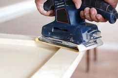 Орбитальный шлифовальный прибор в пользе, зашкурить старая дверь для новой лижет краски Стоковое фото RF