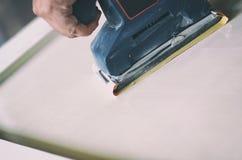 Орбитальный шлифовальный прибор в пользе, зашкурить старая дверь для новой лижет краски Стоковые Фотографии RF