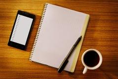Организатор и тетрадь с чашкой кофе на столе Стоковое Изображение RF