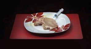 Организм концепции genetically доработанный: шприц и мясо стоковые фото